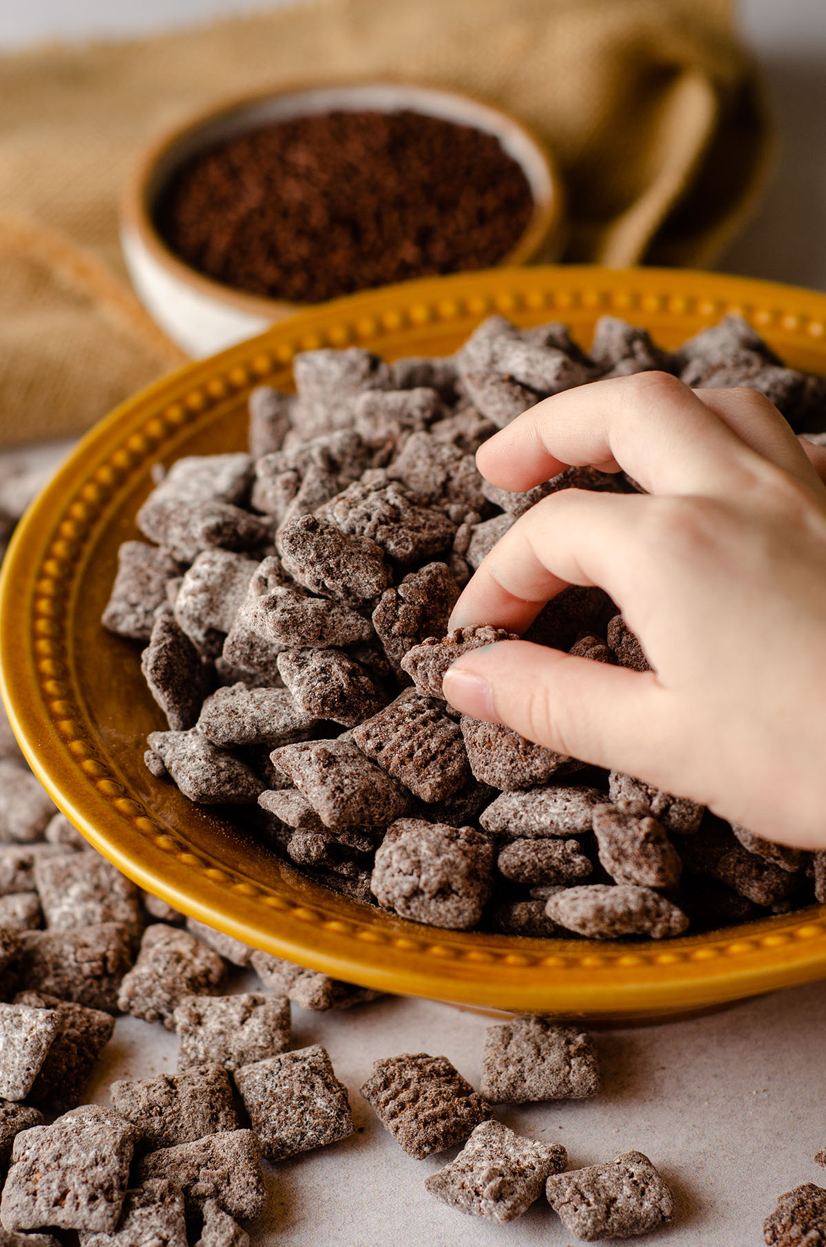 toddler hand grabbing brownie batter puppy chow from a bowl
