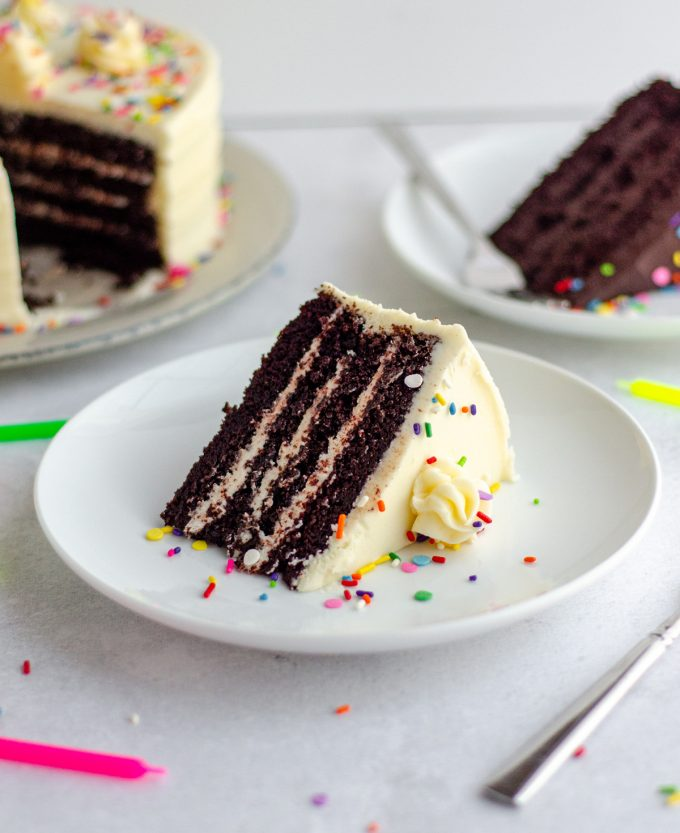 chocolate layer cake with vanilla buttercream and rainbow sprinkles on a white plate