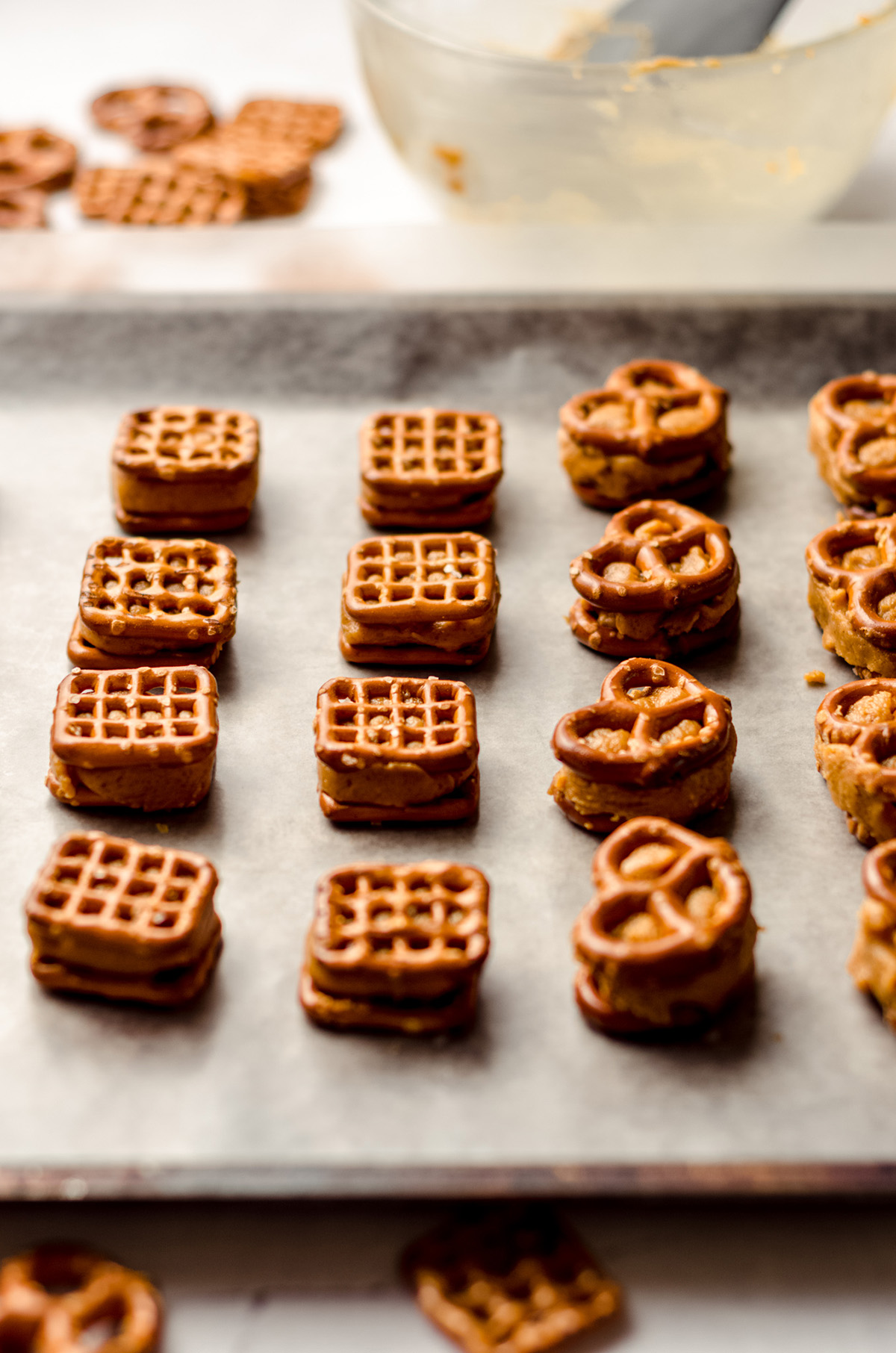 pumpkin peanut butter pretzel bites lined up on a baking sheet