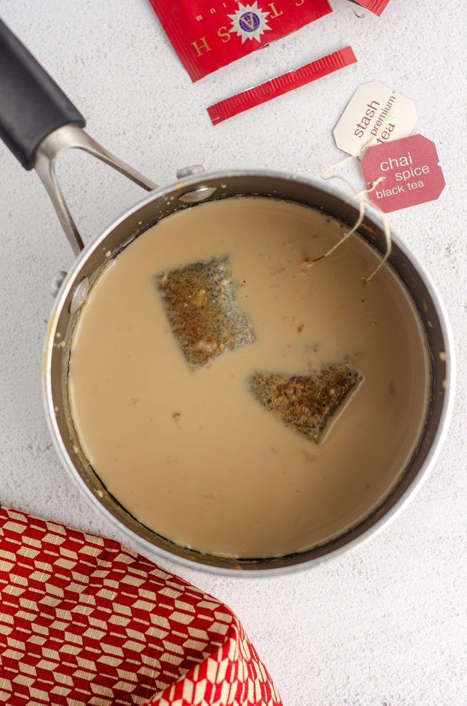aerial view of chai tea bags steeping in milk in a pot