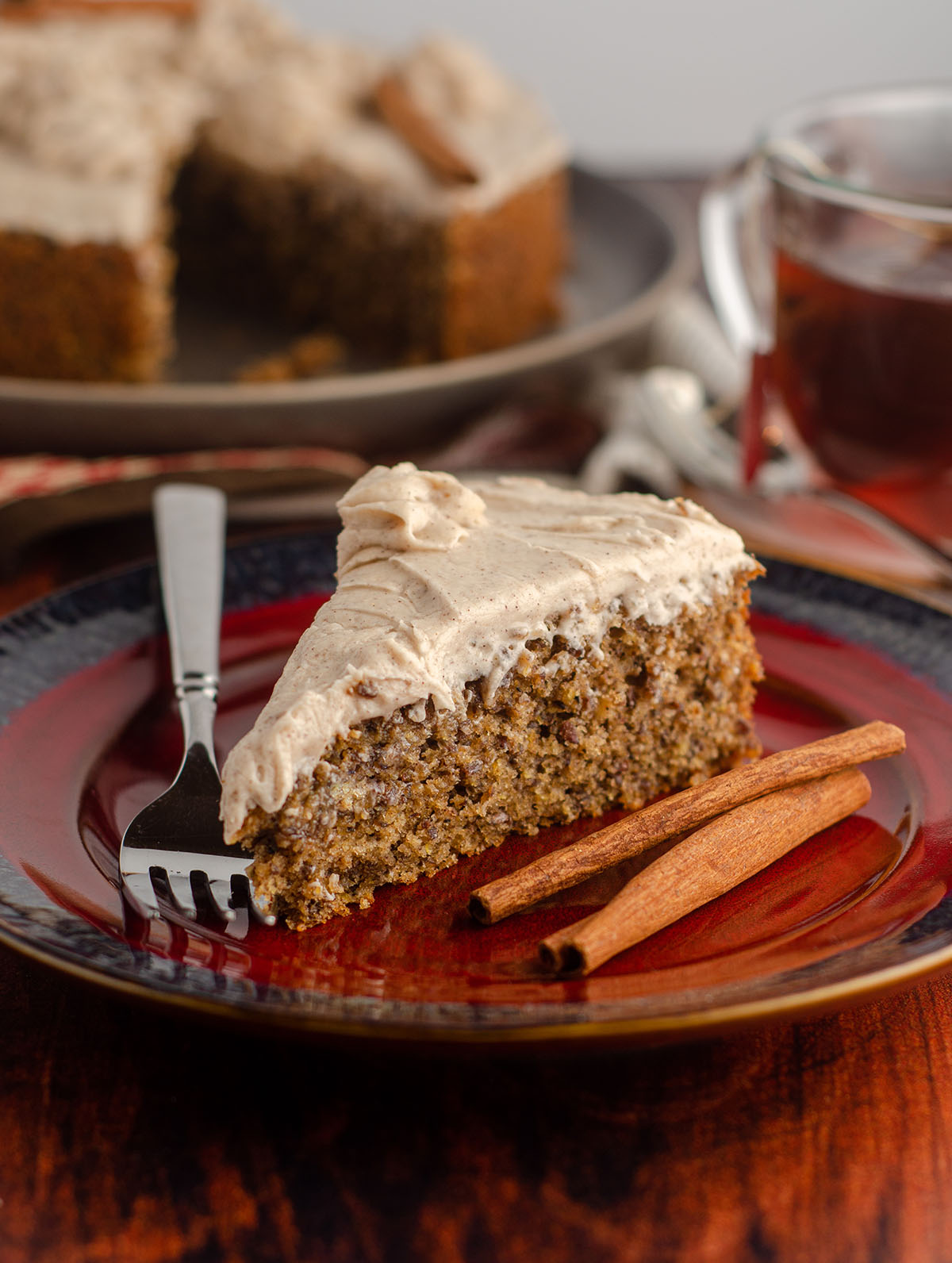 side view of slice of chai cake with cinnamon sticks and a fork