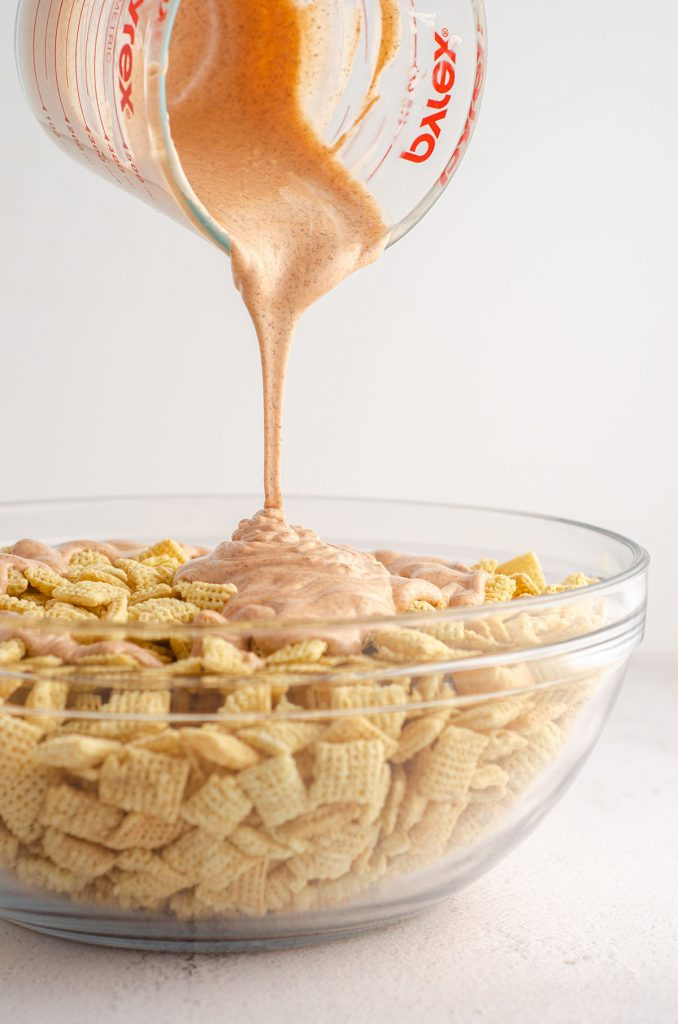 chex sitting in a glass bowl and orange candy melts being poured over them for pumpkin spice puppy chow