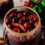 cranberry and orange winter sangria sitting in a glass with a cinnamon sugared rim