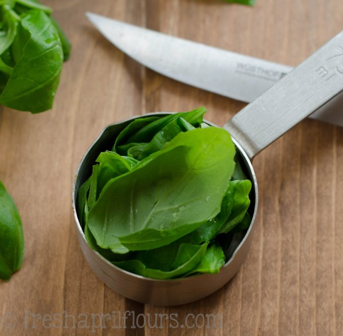 basil leaves in a measuring cup