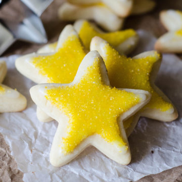 cut out sugar cookies in the shapes of stars with yellow sprinkles