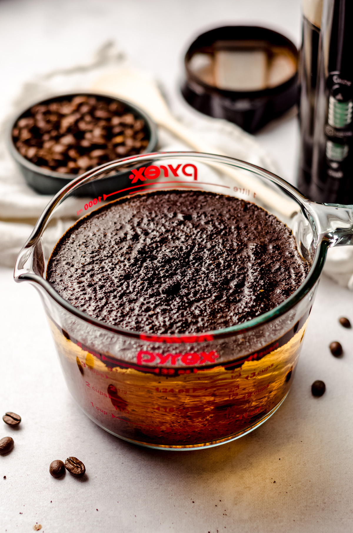 coffee grounds soaking in water in a glass measuring cup