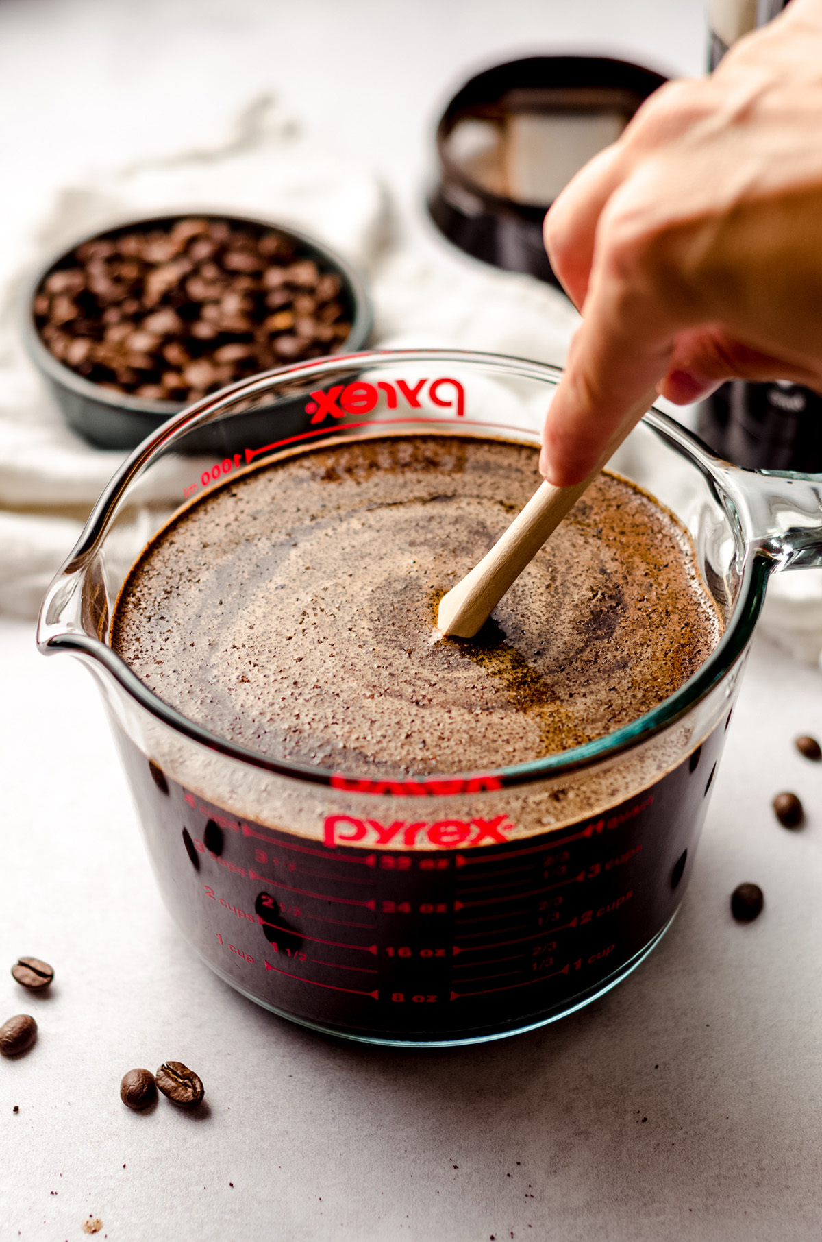 stirring soaked coffee grounds in a glass measuring cup