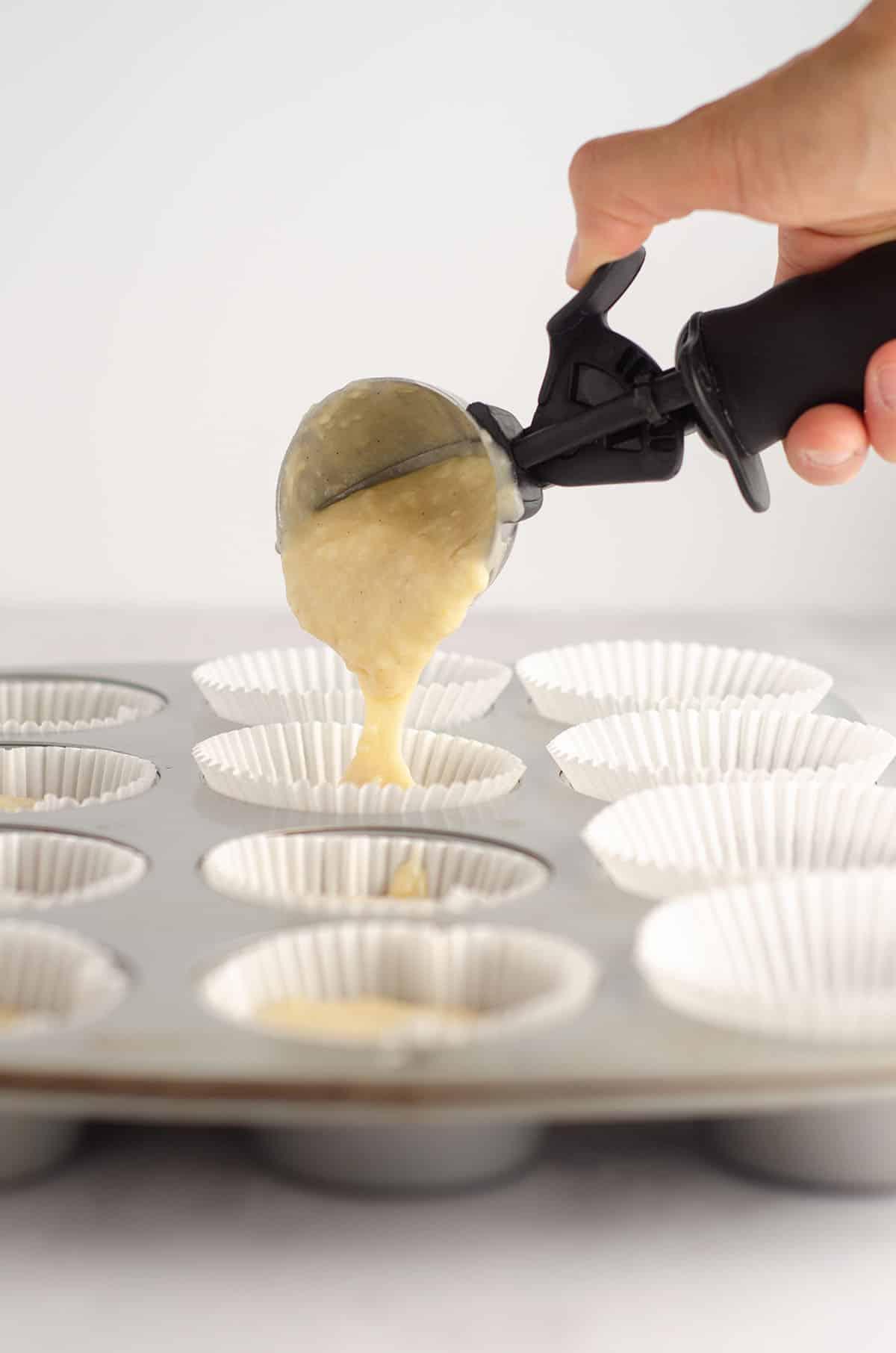 ice cream scooper putting vanilla bean cupcake batter into liners