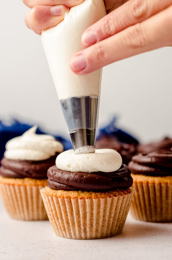 piping marshmallow buttercream onto a s'mores cupcake