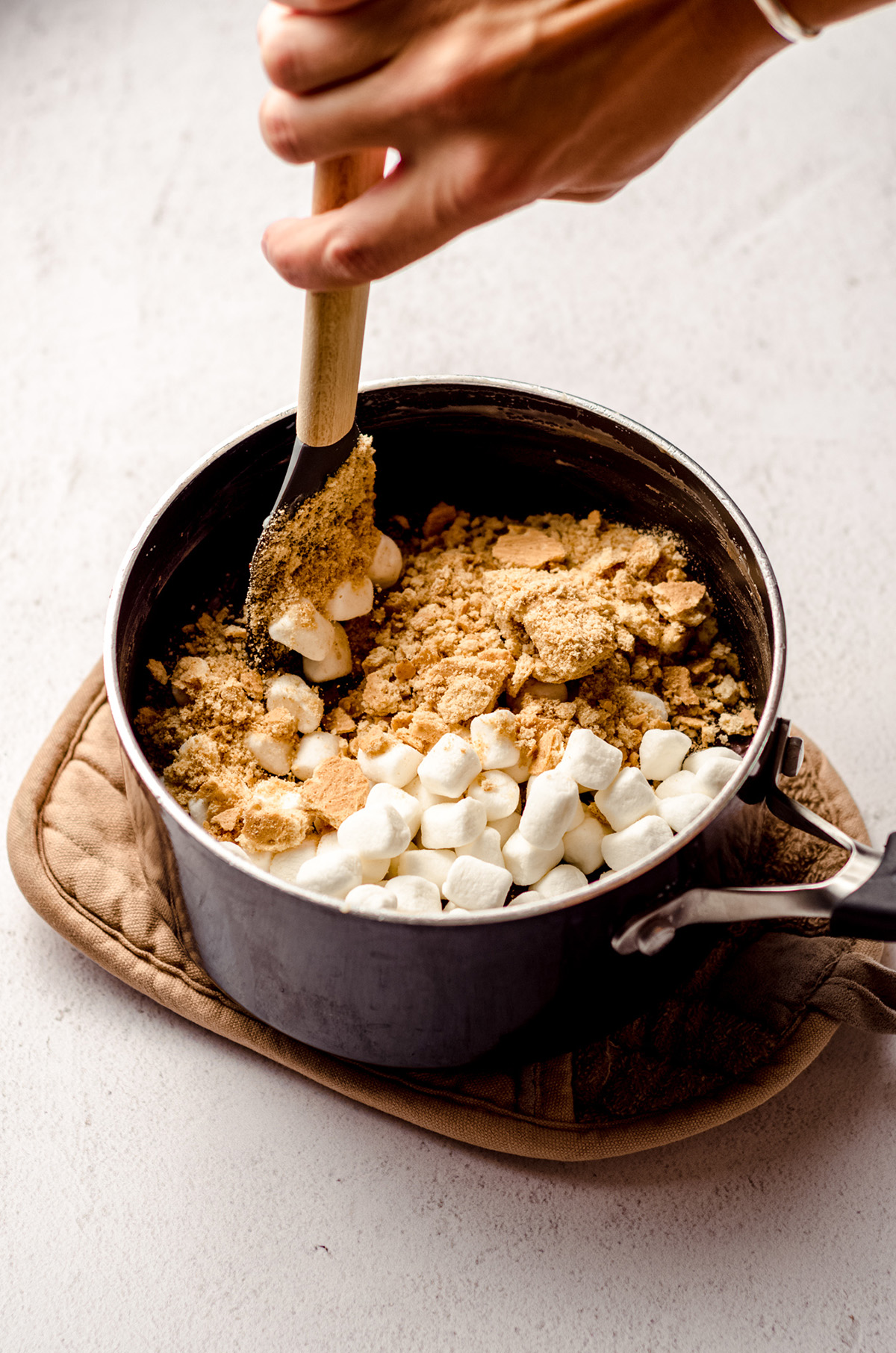 stirring ingredients for s'mores fudge in a saucepan