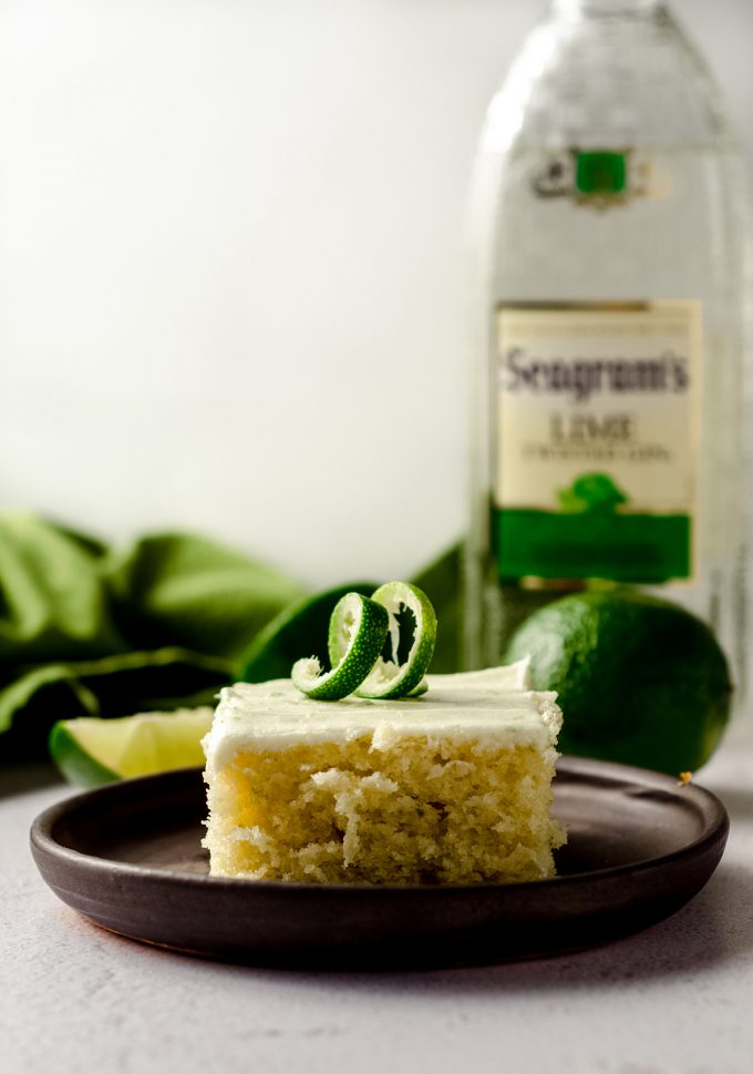 slice of gin and tonic cake sitting on a plate with a bottle of gin and limes in the background