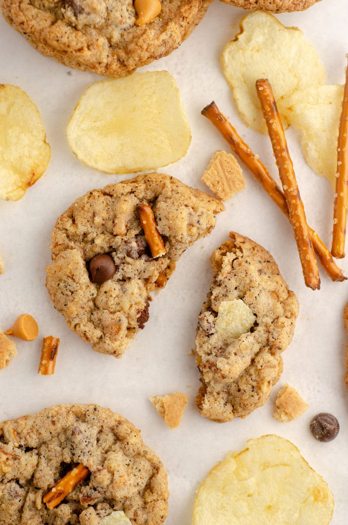 aerial photo of compost cookie scattered with pretzels, chips, butterscotch chips, chocolate chips, and graham cracker pieces