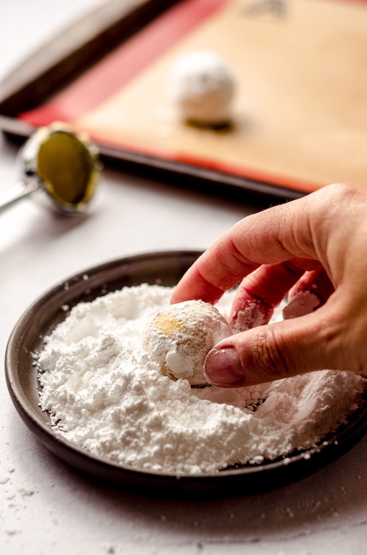 hand rolling a lemon crinkle cookie dough ball in powdered sugar