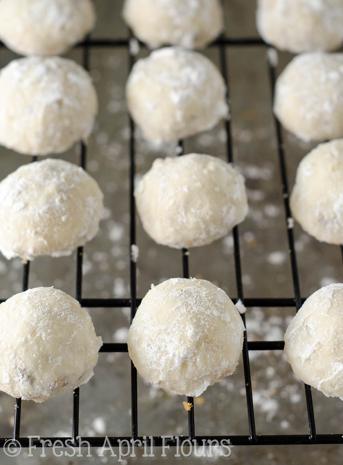 russian tea cakes on a wire cooling rack ready to get rolled in powdered sugar
