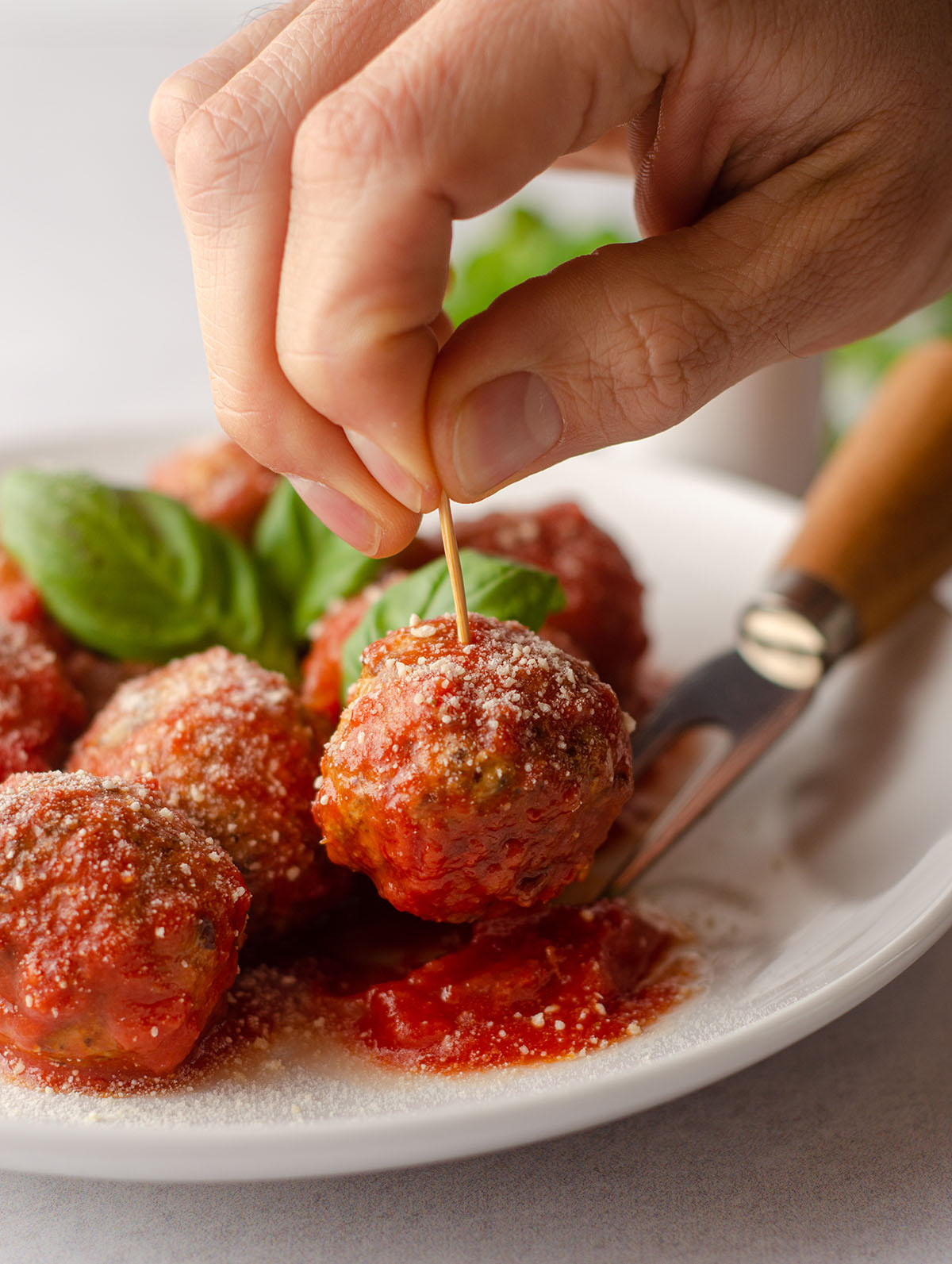 hand sticking a toothpick into a gluten free meatball