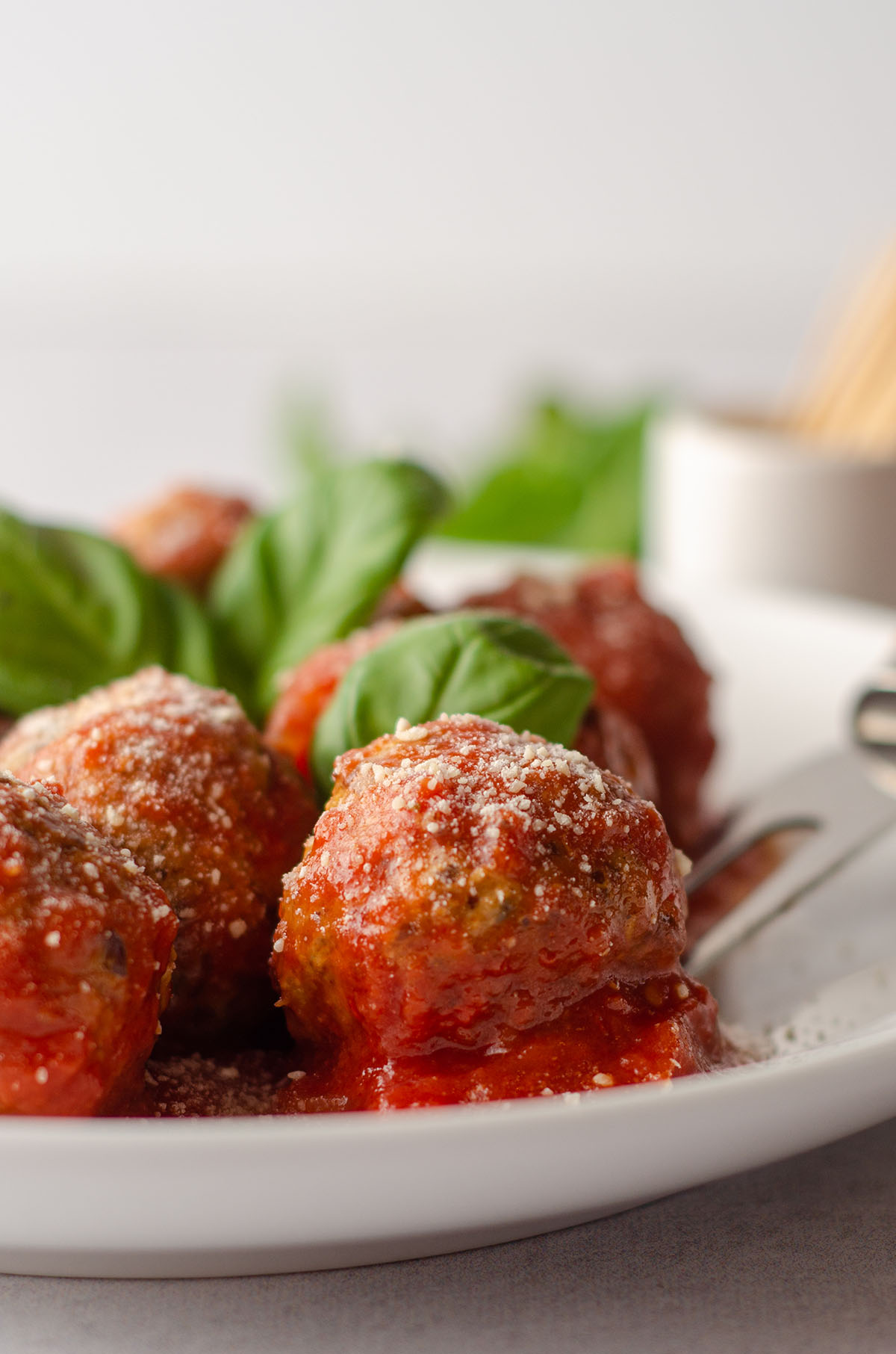 gluten free meatballs on a plate with basil leaves and a serving fork