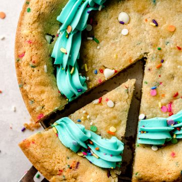 aerial photo of funfetti sugar cookie cake with a slice being taken out of it