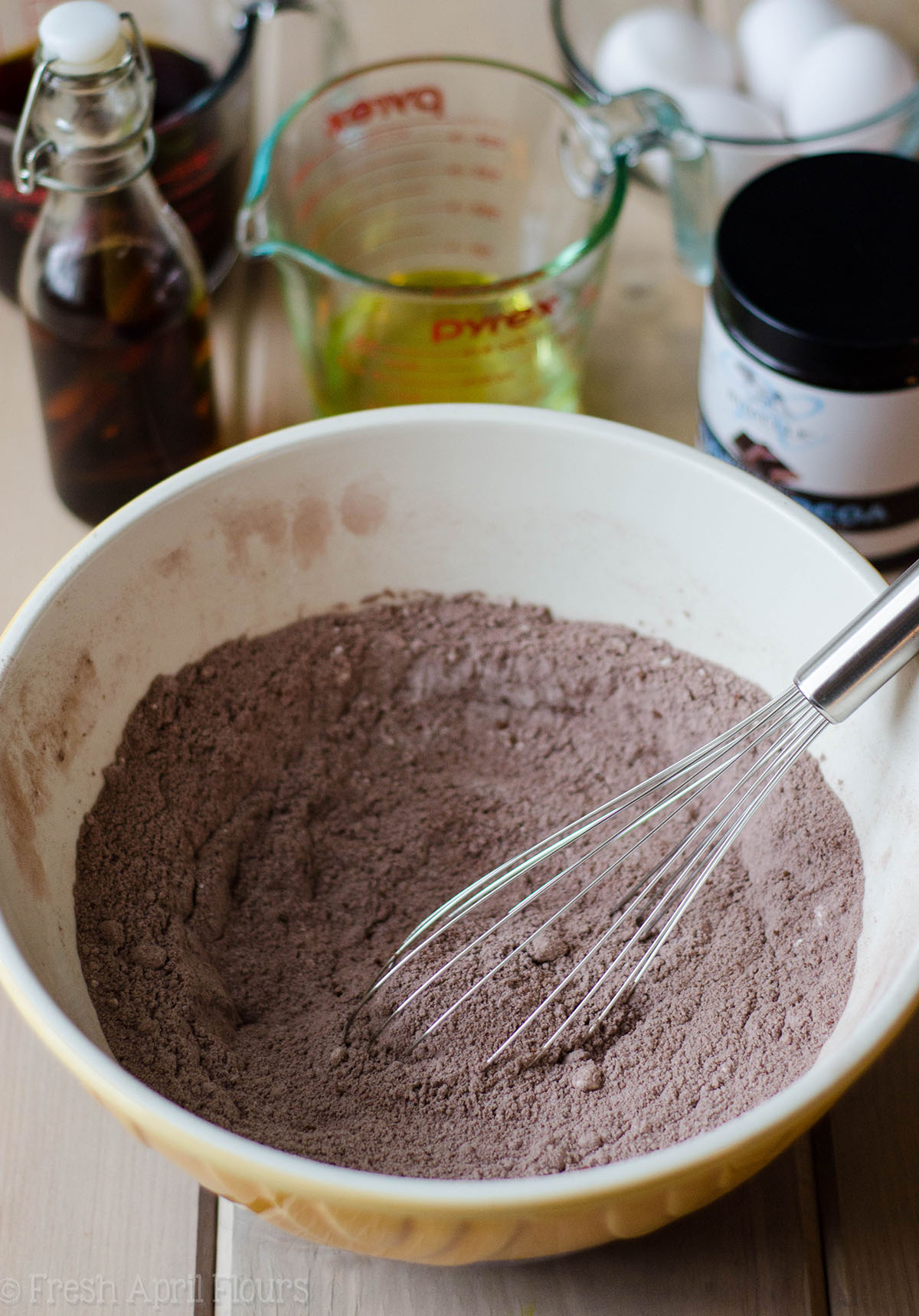 dry batter for simple chocolate cupcakes in a ceramic bowl with a metal whisk