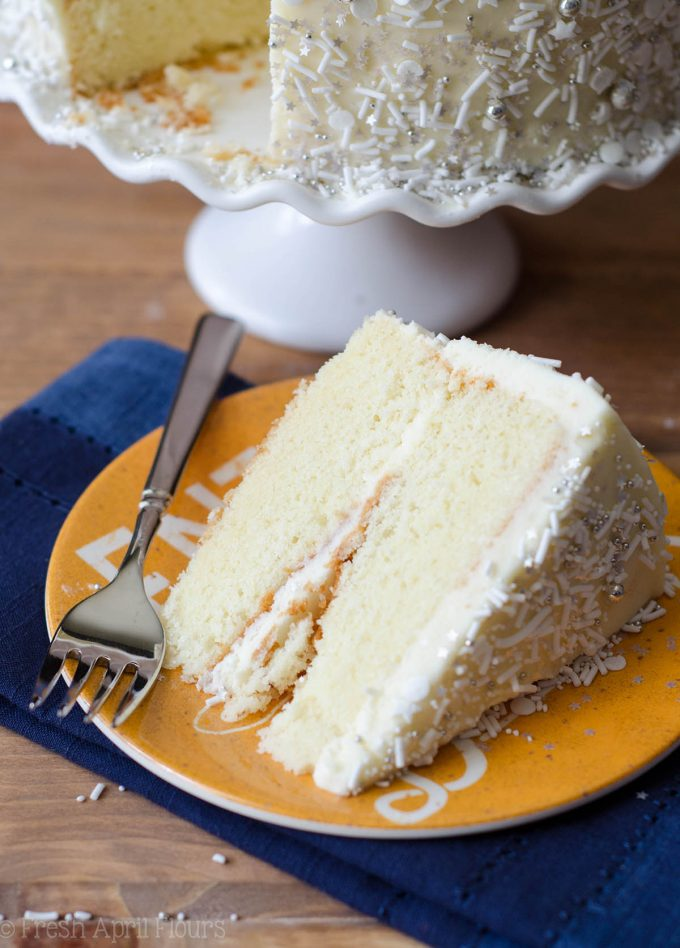 white layer cake with whipped cream buttercream sitting on a yellow plate with a fork