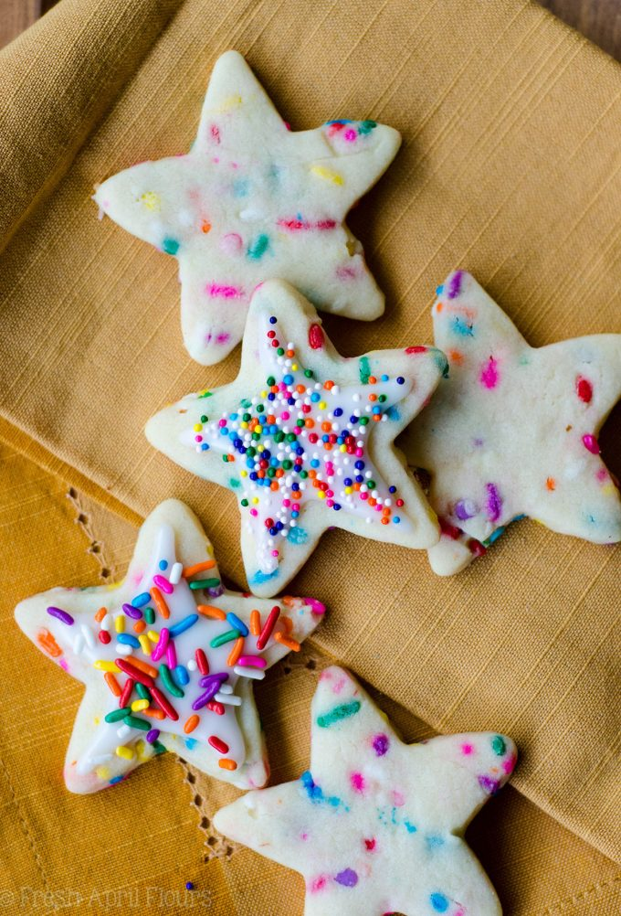 aerial photo of star shaped funfetti sugar cookies decorated with icing and rainbow sprinkles
