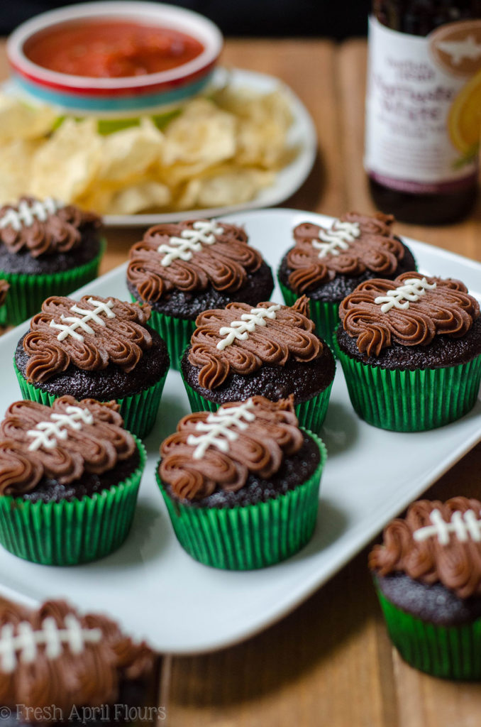 chocolate cupcakes in green cupcake liners with a chocolate frosting footballs piped on top to make football cupcakes
