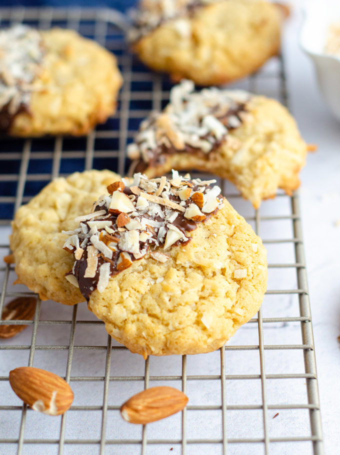 coconut almond cookies dipped in chocolate and garnished with flaked coconut