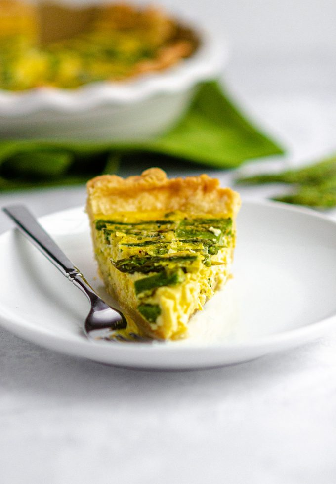 slice of asparagus quiche on a white plate with a fork
