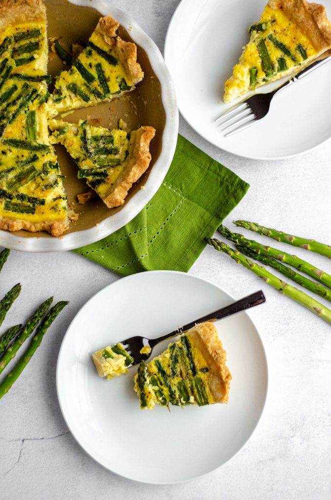 aerial photo of a slice of asparagus quiche on a white plate with a fork and a bite taken out of the slice