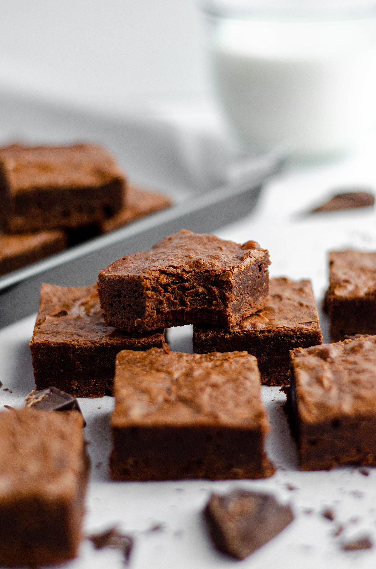 homemade fudgy brownies in a pile and one on top has a bite taken out of it