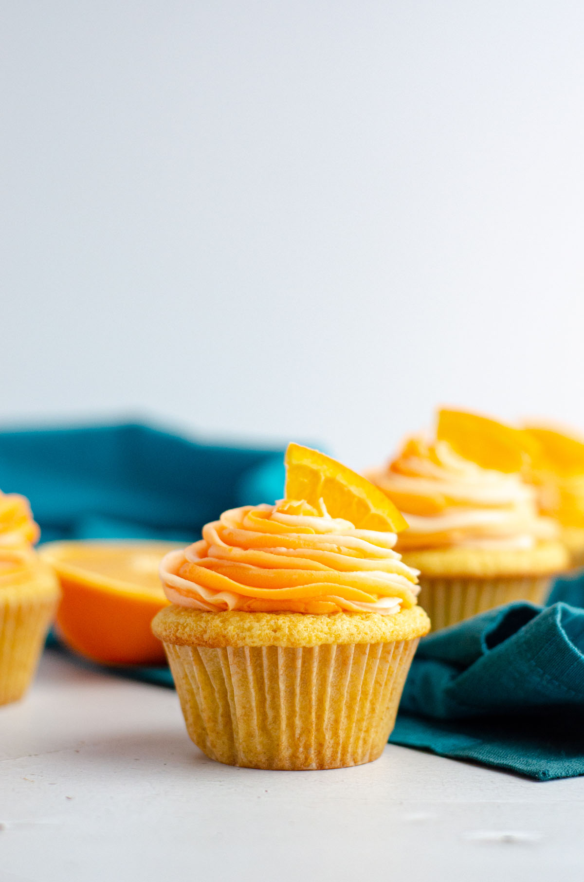 orange creamsicle cupcake in front of a turquoise kitchen towel and orange slices