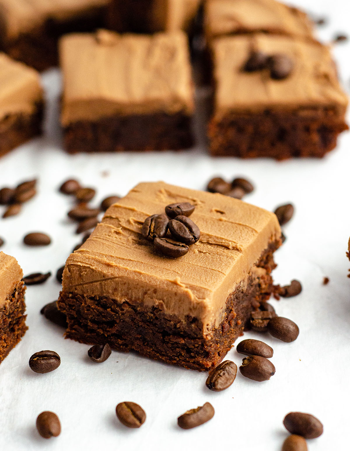 coffee brownie with mocha frosting and coffee beans on top of it for garnish