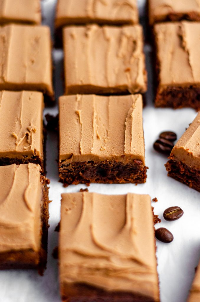 coffee brownies with mocha frosting sliced and on a white surface