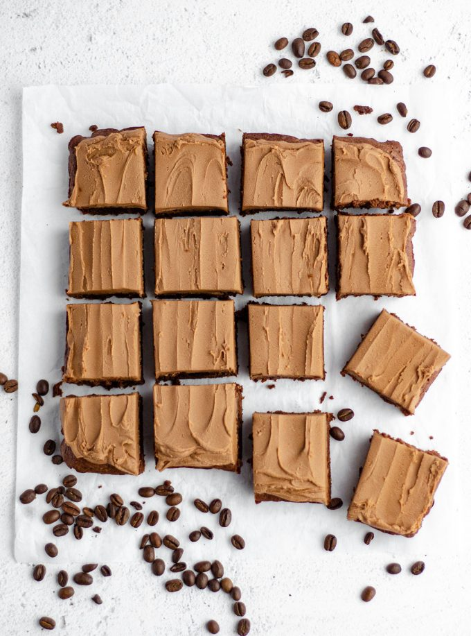 aerial photo of coffee brownies with mocha frosting sliced and sitting on white parchment with coffee beans scattered around