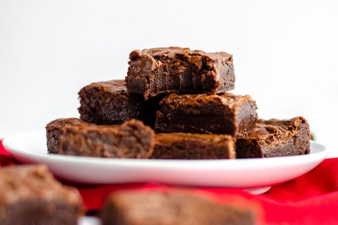 plate of fudgy nutella brownies with one on the top with a bite taken out of it