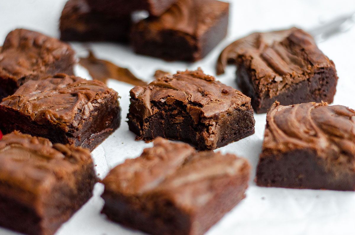 fudgy nutella brownies on a white surface and one with a bite taken out of it