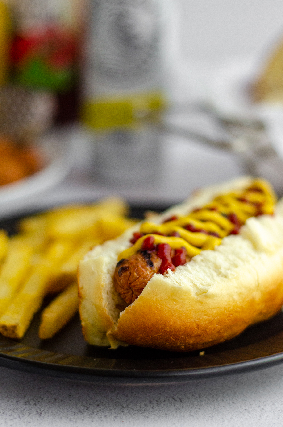hot dog in a homemade hot dog bun with a squirts of ketchup and mustard sitting on a black plate with french fries
