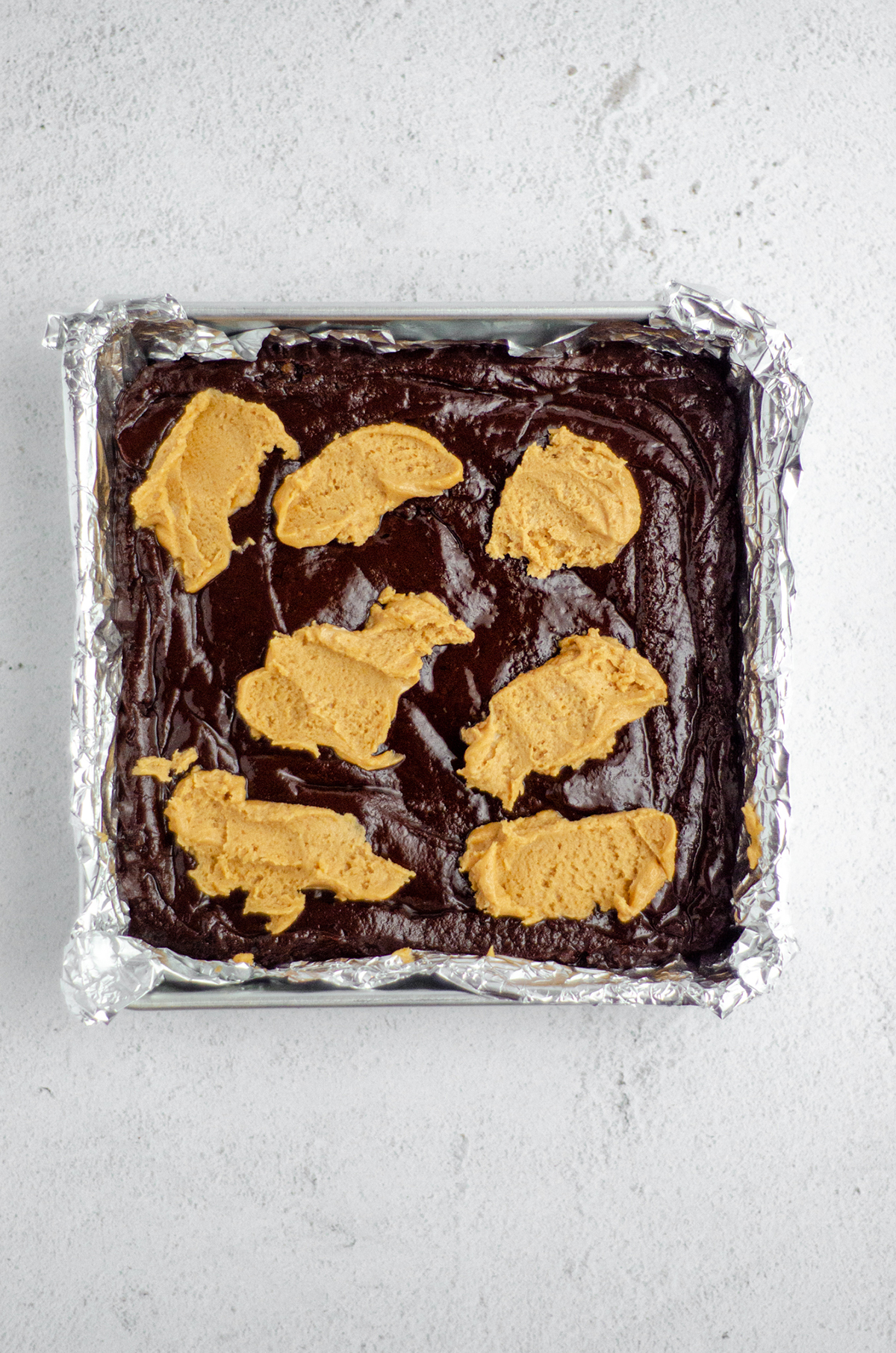 peanut butter cookie dollops on top of brownie batter to make peanut butter cookie brownies