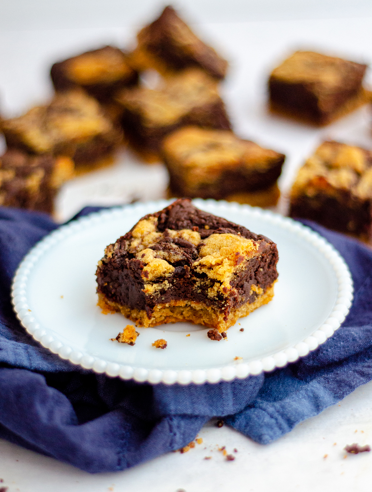 peanut butter cookie brownie sitting on a plate with a bite taken out of it and more brownies in the background