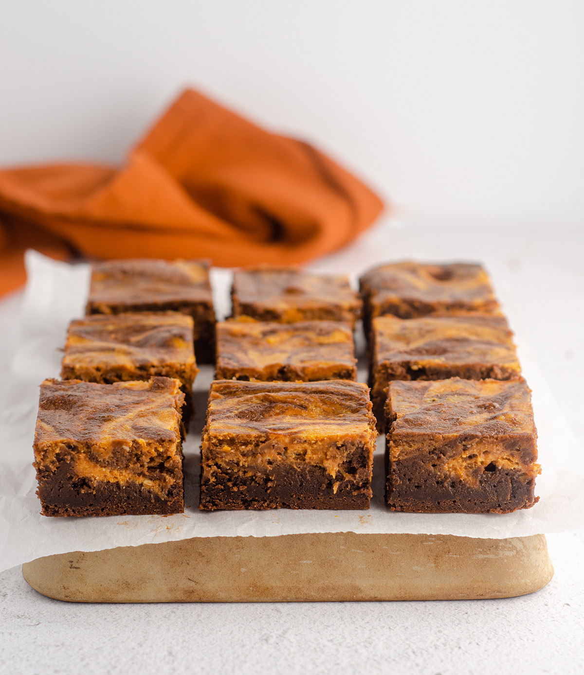 sliced pumpkin cheesecake brownies on a platter