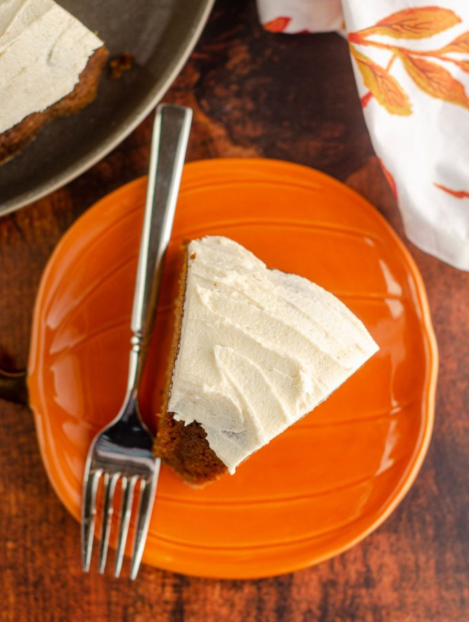 aerial photo of a slice of pumpkin bundt cake with browned butter buttercream sitting on an orange pumpkin plate