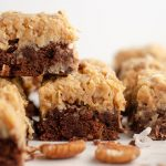 stack of german chocolate brownies with pecans and coconut scattered around