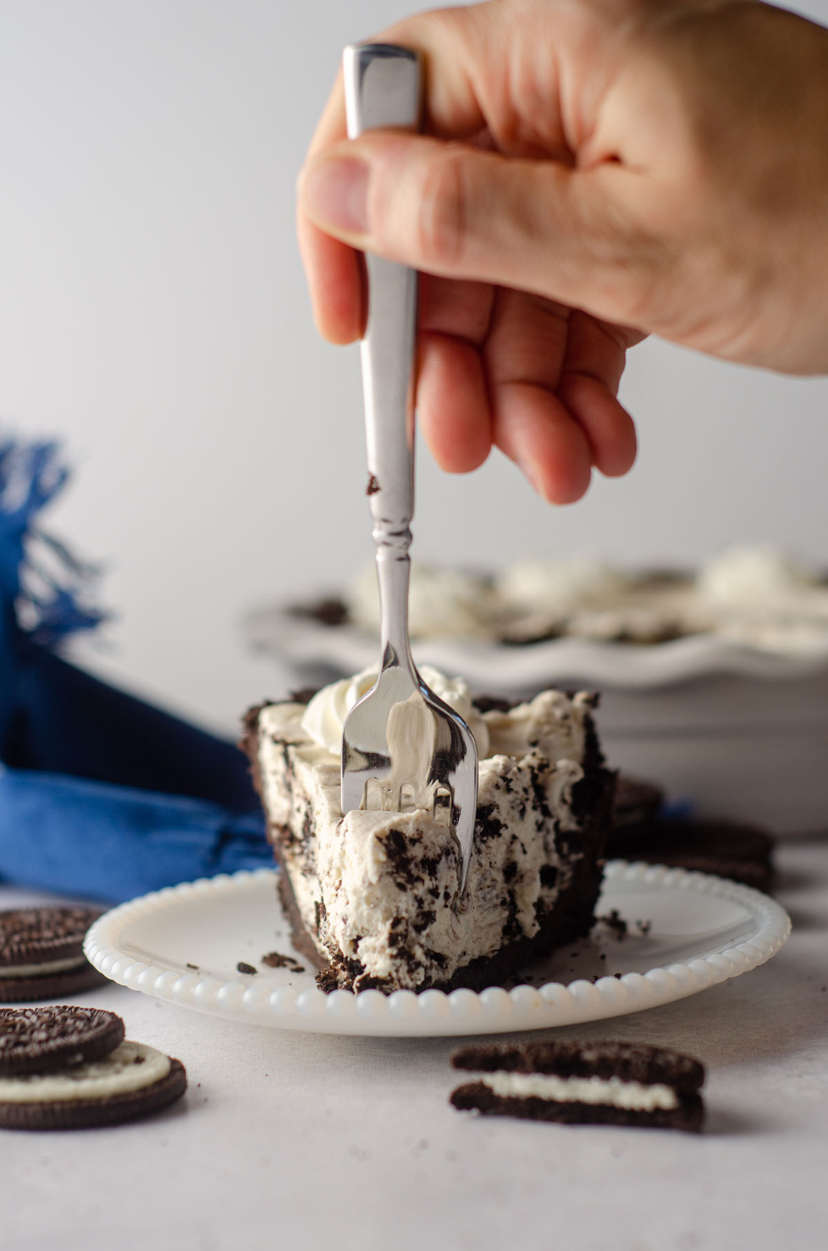 hand using a fork to dig into a slice of no bake oreo pie