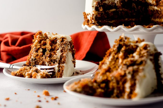 two slices of carrot walnut cake on plates and one has a fork digging into it