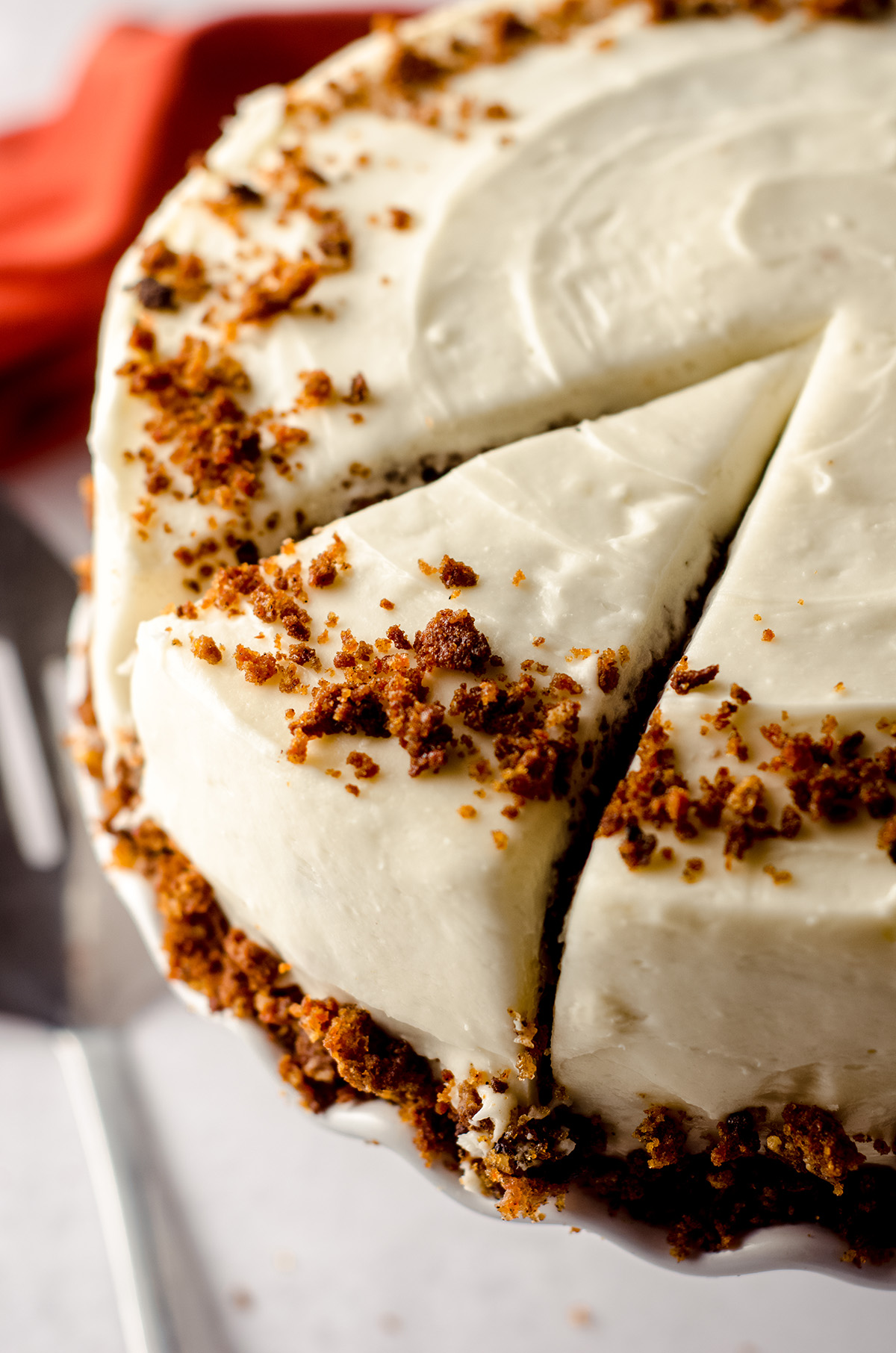carrot walnut cake on a cake stand and cuts made for a slice to serve
