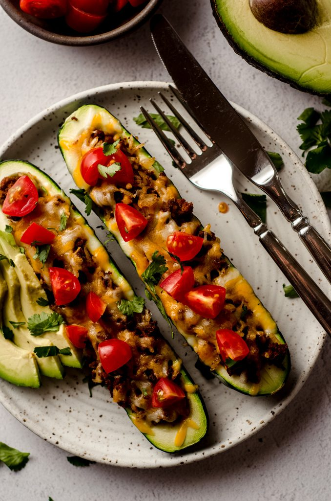 aerial photo of taco zucchini boats on a plate with a fork and a knife