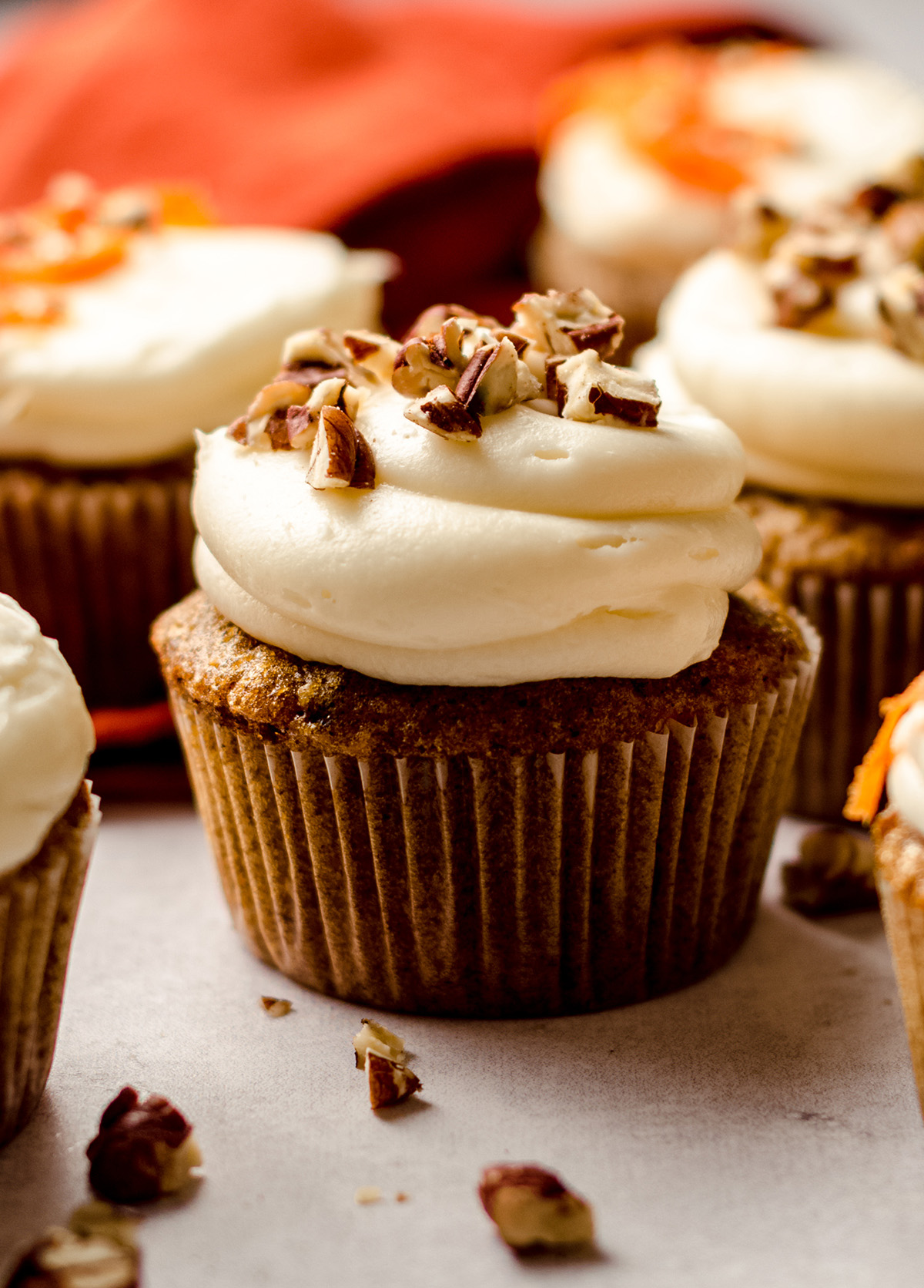 carrot cake cupcakes with cream cheese frosting with pecans on top