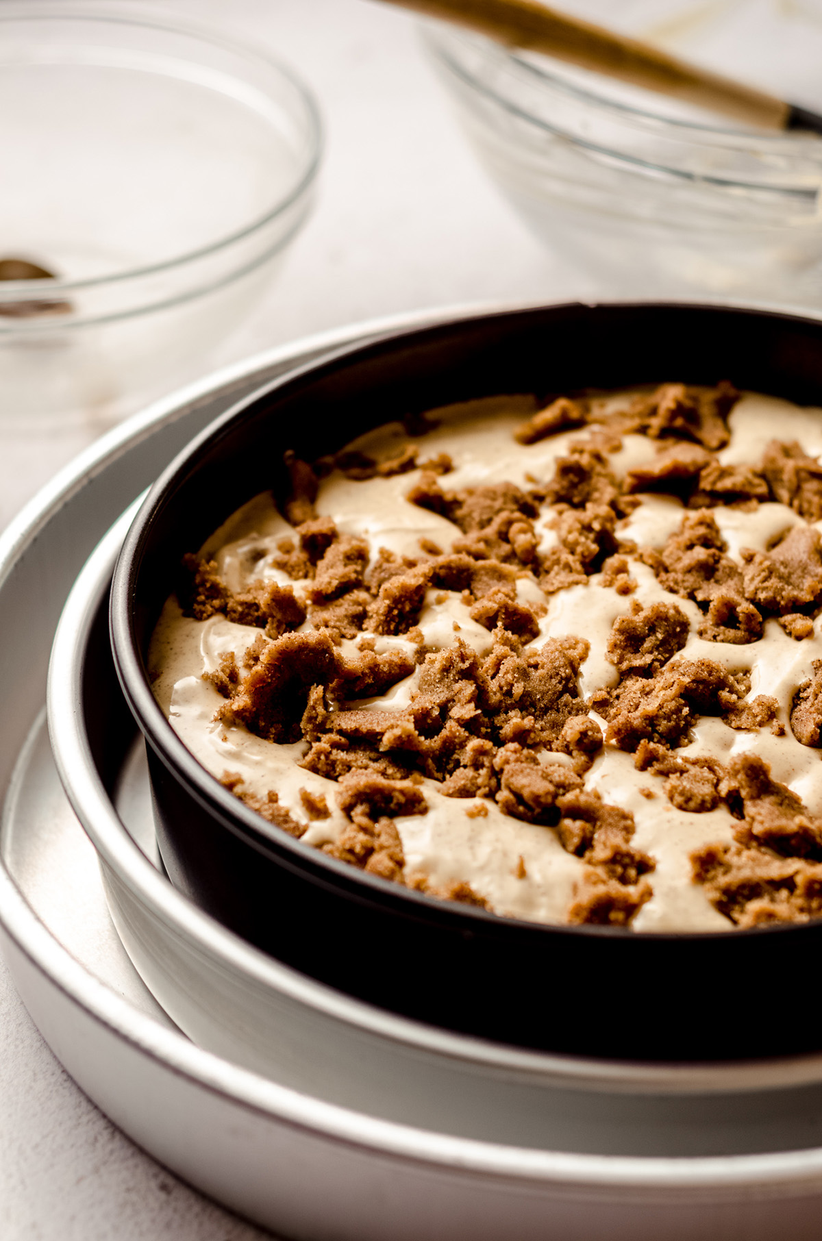 cinnamon roll cheesecake batter with chunks of cinnamon roll filling ready to bake