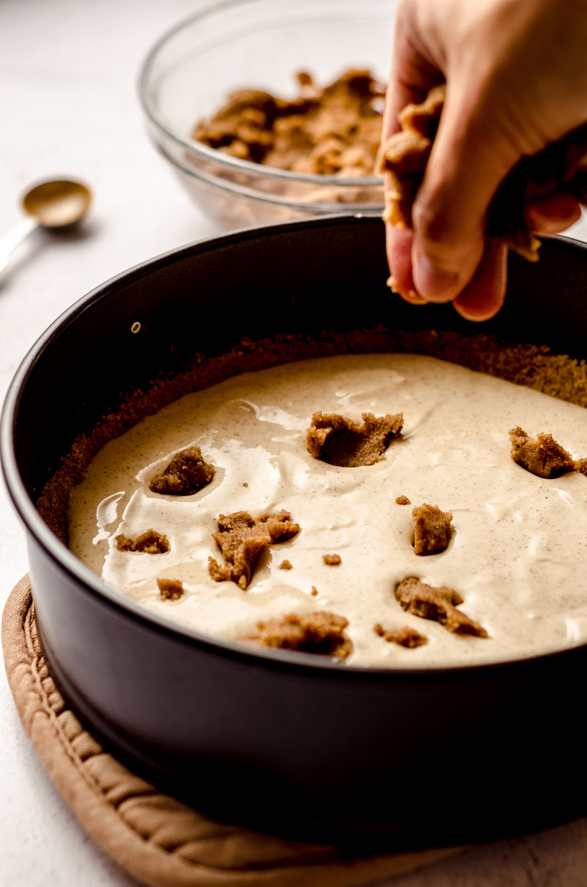 hand dropping chunks of cinnamon roll filling into cinnamon roll cheesecake batter