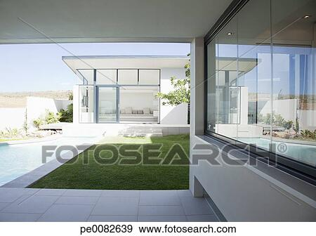 Stock Photograph of Patio and pool adjoining modern house ...