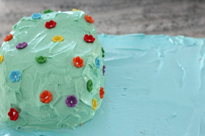 Cover the mountain on your Moana cake with green icing and flowers